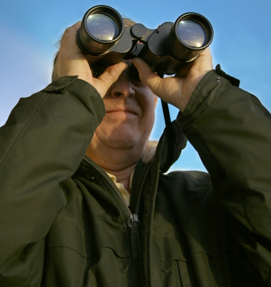 man staring out into the unknown with binoculars